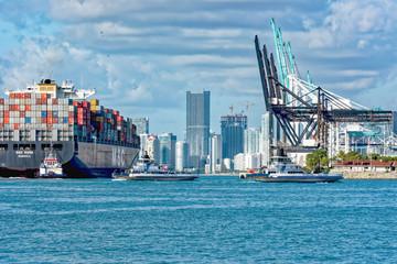 Tug guiding container ship