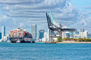 Tug guiding container ship into Port Miami