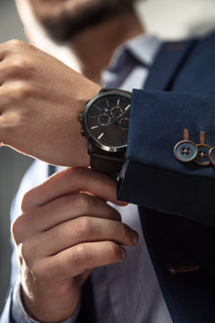 Elegant man with suit and watch on hand.