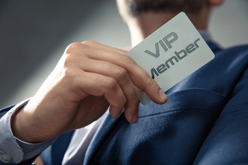 VIP member card holded by an elegant man in suit.