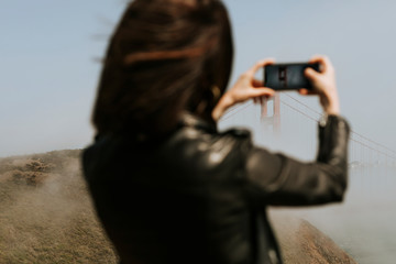 Woman taking a photograph of the Golden Gate Bridge, San Francisco