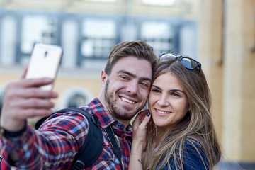 Happy couple of tourists taking selfie in showplace of city. Man and woman making photo on city background