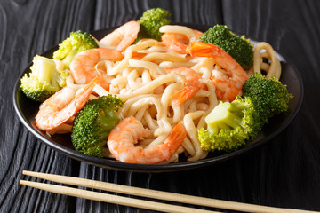 Asian food delicious udon with shrimp, broccoli and soy sauce close-up on a black table. horizontal