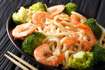 Healthy food: udon noodles with shrimps, broccoli and soy sauce close-up on a plate. horizontal