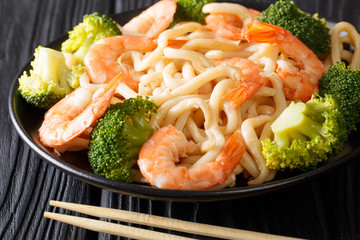 Delicious Asian udon noodles with shrimps and broccoli closeup on a plate. horizontal