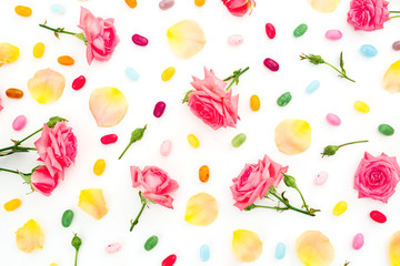Bright pattern of roses flowers and petals with colorful sugar candy on white background. Flat lay, top view.