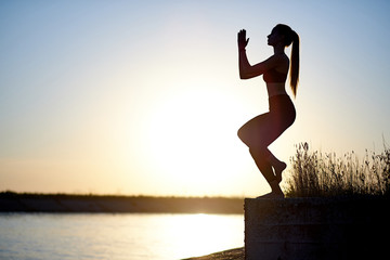 Silhouette woman practicing yoga or stretching on the beach pier at sunset or sunrise