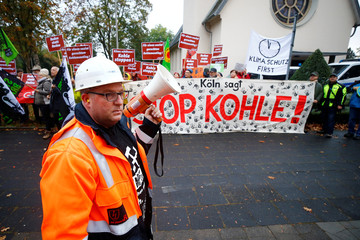 Employee of German utility RWE holds a bullhorn at a labour protest, as environmentalists demonstrate behind him, in the Rhenish lignite mining area, in Bergheim