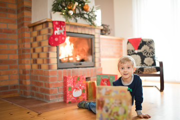 5 years old boy lies in front of the fireplace and is happy happy with Christmas gifts.