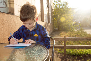 Boy doing homework outdoors