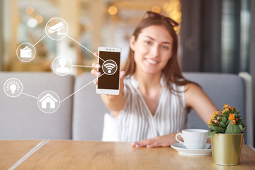 Woman using modern mobile smart phone connecting to wifi automation apps. Remote virtual control at home.