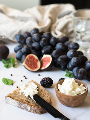 Rye bread and a knife with cream cheese and various fruits on a marble background. Cooking toast with cheese and berries.