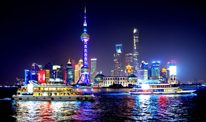 colorful lights and futuristic skyline and boats on river of shanghai pudong skyscrapers, China