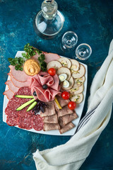 Cold smoked meat plate with prosciutto, salami, bacon, pork chops, cheese and olives on gray stone background.