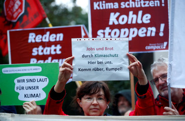 Environmentalist holds a poster as employees of German utility RWE attend a labour protest next to her in Bergheim