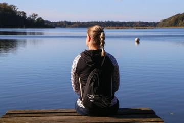 Frau sitzt entspannt an einem See und genießt den Blick in die Natur
