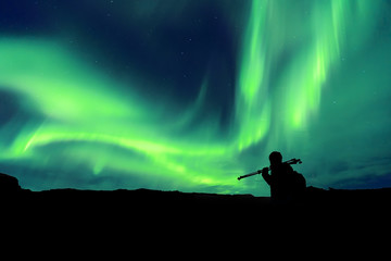 Aurora borealis with silhouette standing photographer on the mountain.Freedom traveller journey concept