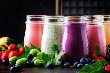 Healthy and useful colorful berry cokctalis, smoothies and milkshakes with yogurt, fresh fruit and berries on brown table, selective focus