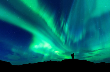 Foto op Textielframe Noorderlicht Aurora borealis with silhouette love romantic couple on the mountain.Honeymoon travel concept