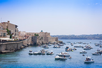 Syracuse, Sicily, Italy – august 12, 2018: people float on boats and bathe in the sea near the Ortygia (Ortigia) Island