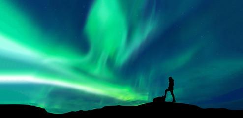 Tuinposter Noorderlicht Aurora borealis with silhouette standing man on the mountain.Freedom traveller journey concept
