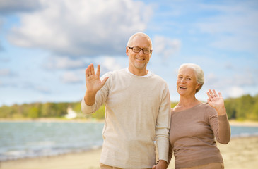 old age, retirement and people concept - happy senior couple waving hands over beach background