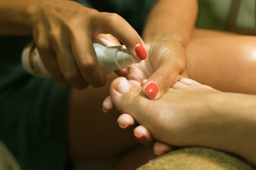 Female pedicure. Care for feet and toenails. Master conducts procedures for foot care.