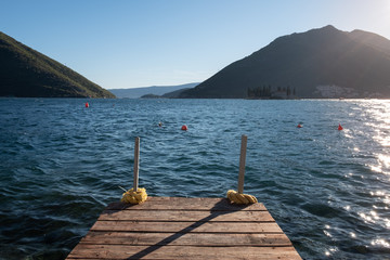 Wooden pier at the blue water of Kotor bay. Exit to the Adriatic sea. Montenegro