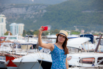 Europe travel selfie, cute happy smiling tourist girl taking self-portrait picture with smartphone during summer vacation in famous European Mediterranean destination.