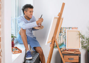 Young African-American artist painting picture at home