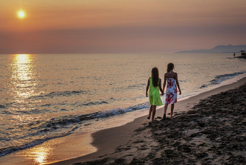 Two little girls walking together on the beach in the sunset