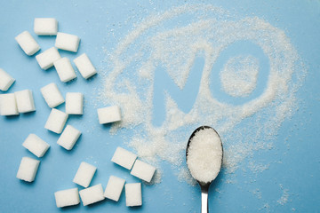 Sugar Cubes, Spoon And Letters NO On The Pastel Blue Background. Concept Of Sweet Drinks, Diet, Diebetes, Refined Sugar Free. Top View Minimal Flat Lay