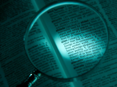MAGNIFYING GLASS ON DICTIONARY PAGE SHOWING DEFINITION OF THE WORD ALIEN