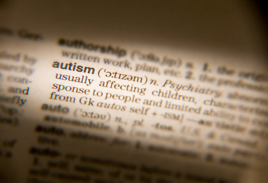 MAGNIFYING GLASS ON DICTIONARY PAGE SHOWING DEFINITION OF THE WORD AUTISM