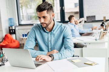 handsome bearded young businessman using laptop at workplace