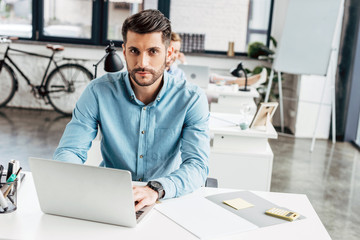 handsome young businessman using laptop and looking at camera in office