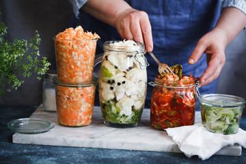 Fermented preserved vegetarian food concept. Cabbage kimchi, broccoli marinated, sauerkraut sour glass jars