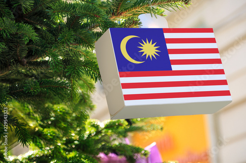 Malaysia flag printed on a Christmas gift box. Printed present box decorations on a Xmas tree branch on a street.