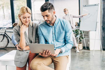 young businessman and businesswoman working with laptop in office