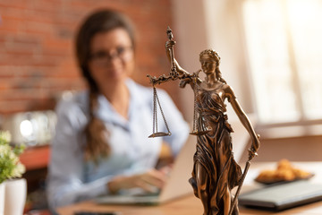 Law concept with Themis and female lawyer in background