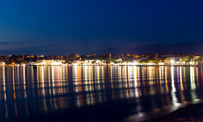 Town of Novalja at night and light reflections in the water, Croatia, Adriatic sea