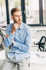 thoughtful young businessman with hand on chin sitting on table and looking away in office