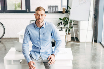 high angle view of handsome young businessman sitting on table and looking at camera in office
