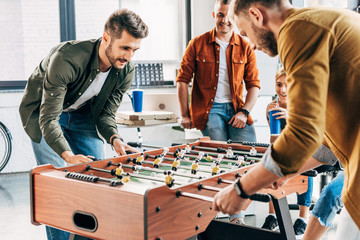 group of young casual businessmen playing table football at office and having fun together
