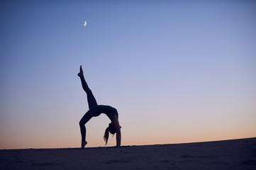 Beautiful young woman practices backbend yoga asana Eka Pada Urdhva Dhanurasana - One Leg Upward facing bow pose in the desert at night