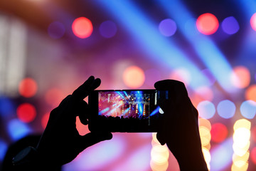 Silhouette of young man, taking photo rock concert on the mobile phone, outdoor fest