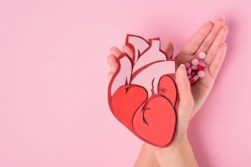 cropped image of woman holding anatomical human heart and various pills on pink