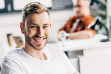 handsome young businessman looking at camera with colleague sitting blurred on background at office