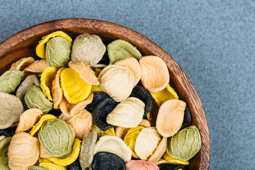 Traditional Italian Rainbow pasta. Colored raw pasta on a stone background