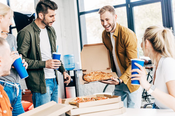 young successful business people having pizza for lunch together while working on startup at office